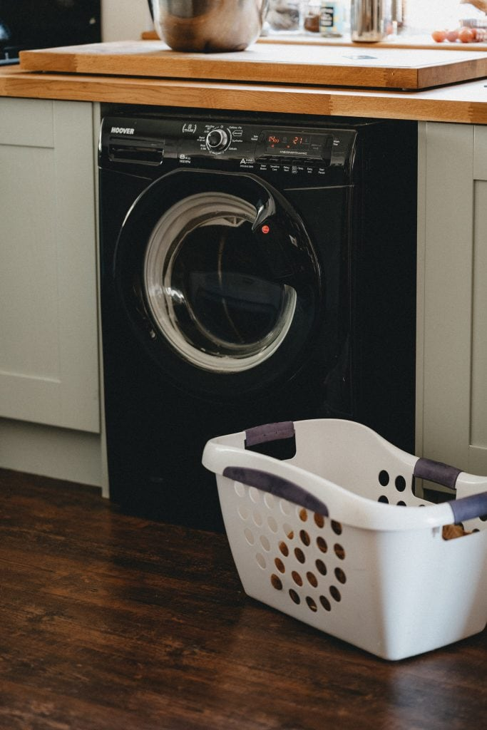 A black washing machine with sage green cabinets on either side, a laundry basket beside and a butcher block counter on the top.
