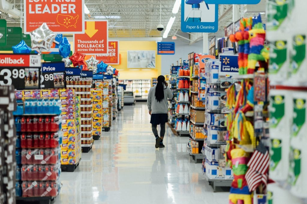 woman walking through a main aisle of walmart with groceries and other various items on each side of her, along with several bright orange rollback sale signs