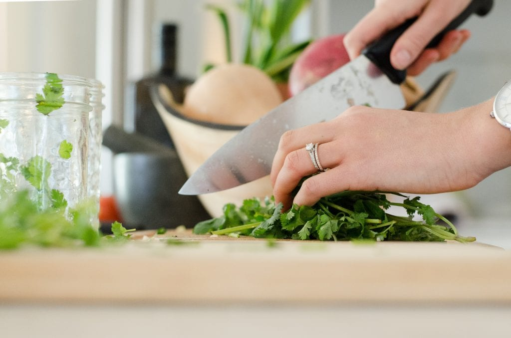 Close-up of hands holding a knife and chopping up greens on a cutting board