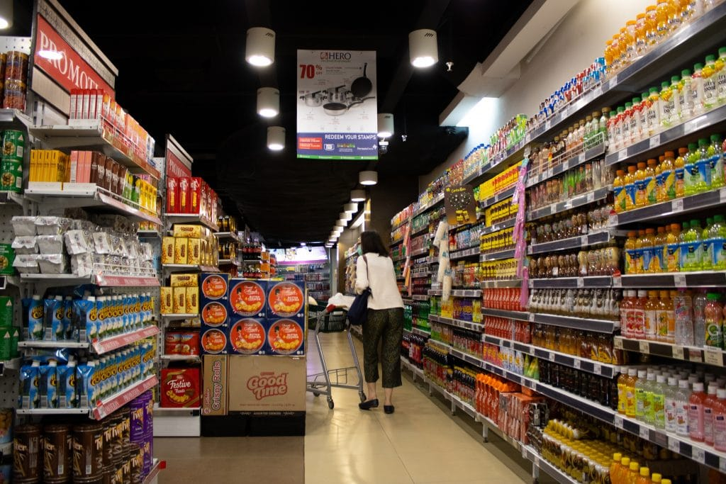 Woman with a shopping cart walking down a grocery store aisle filled with products