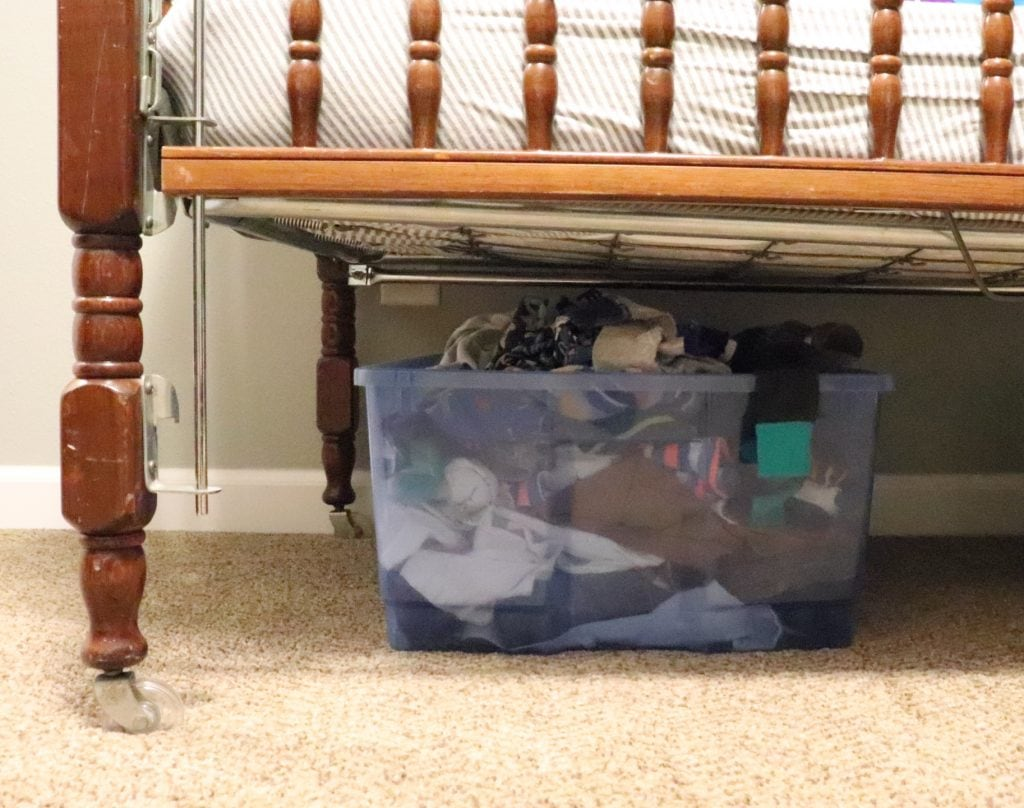 A blue plastic tub full of baby clothes sitting on brown carpet under a brown wooden crib