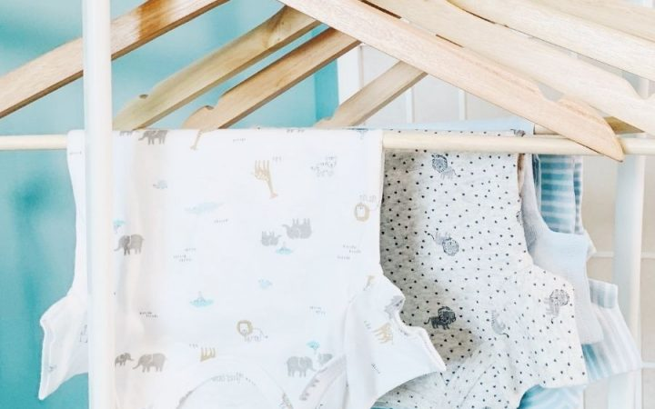 white onesies hanging in a row on wood hangers