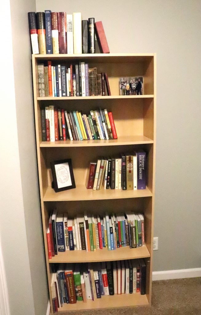 Bookcase against a grey wall with well organized books, a photo and a framed quote on the shelves, as well
