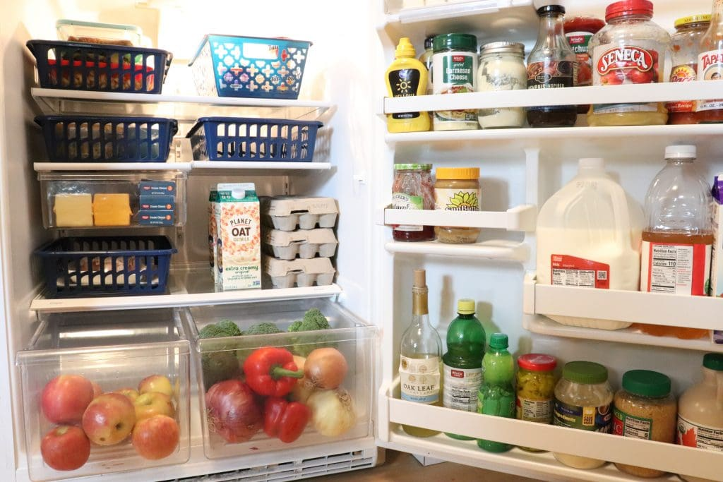 an open fridge with navy baskets on the shelves holding food, an open veg and fruit drawers and condiments and milk in the door shelves.