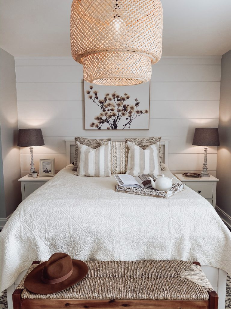 A queen bed with a white coverlet, a shiplap wall behind with a floral painting on it, nightstands with grey lamps on either side, and a wicker light fixture above.